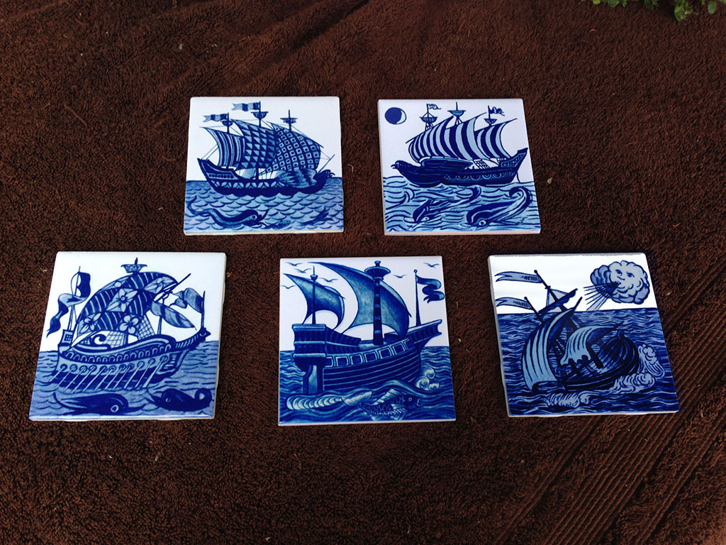 De Morgan ship tiles in cobalt and white. From left: bird ship with multi-pattern sails, bird ship with moon and dolphins, galleon with floral sails and dolphins, British warship with sparkle fish, small sailing ship with cloud