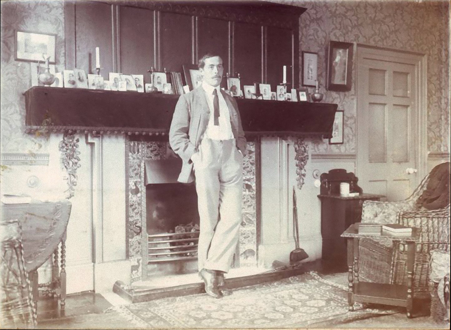 Lewis Carroll standing before his William De Morgan tile fireplace at Christ Church, Oxford